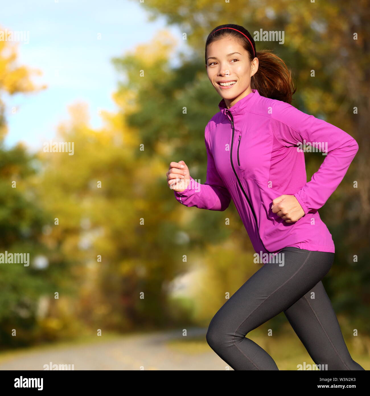 Young Asian woman running female jogger happy. Female runner jogging in park in autumn park forest in fall colors. Beautiful young sport model. Multi-ethnic Asian Chinese / Caucasian girl in her 20s. - Stock Image
