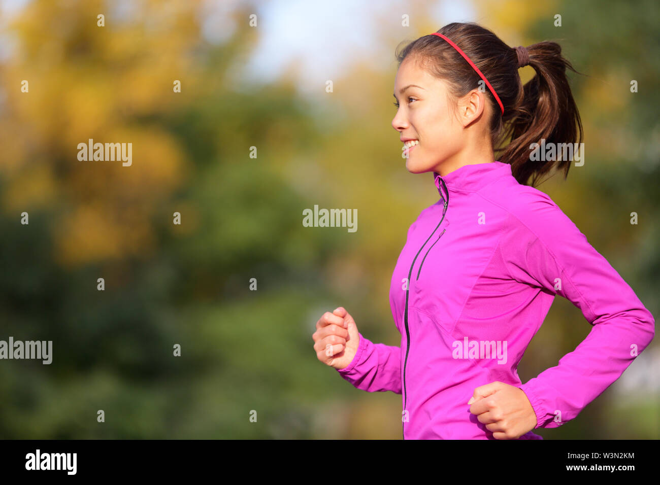 Asian woman running in autumn forest in fall. Female runner training outdoor in warm running outfit. Beautiful multi-ethnic Chinese Asian / Caucasian female jogging. - Stock Image