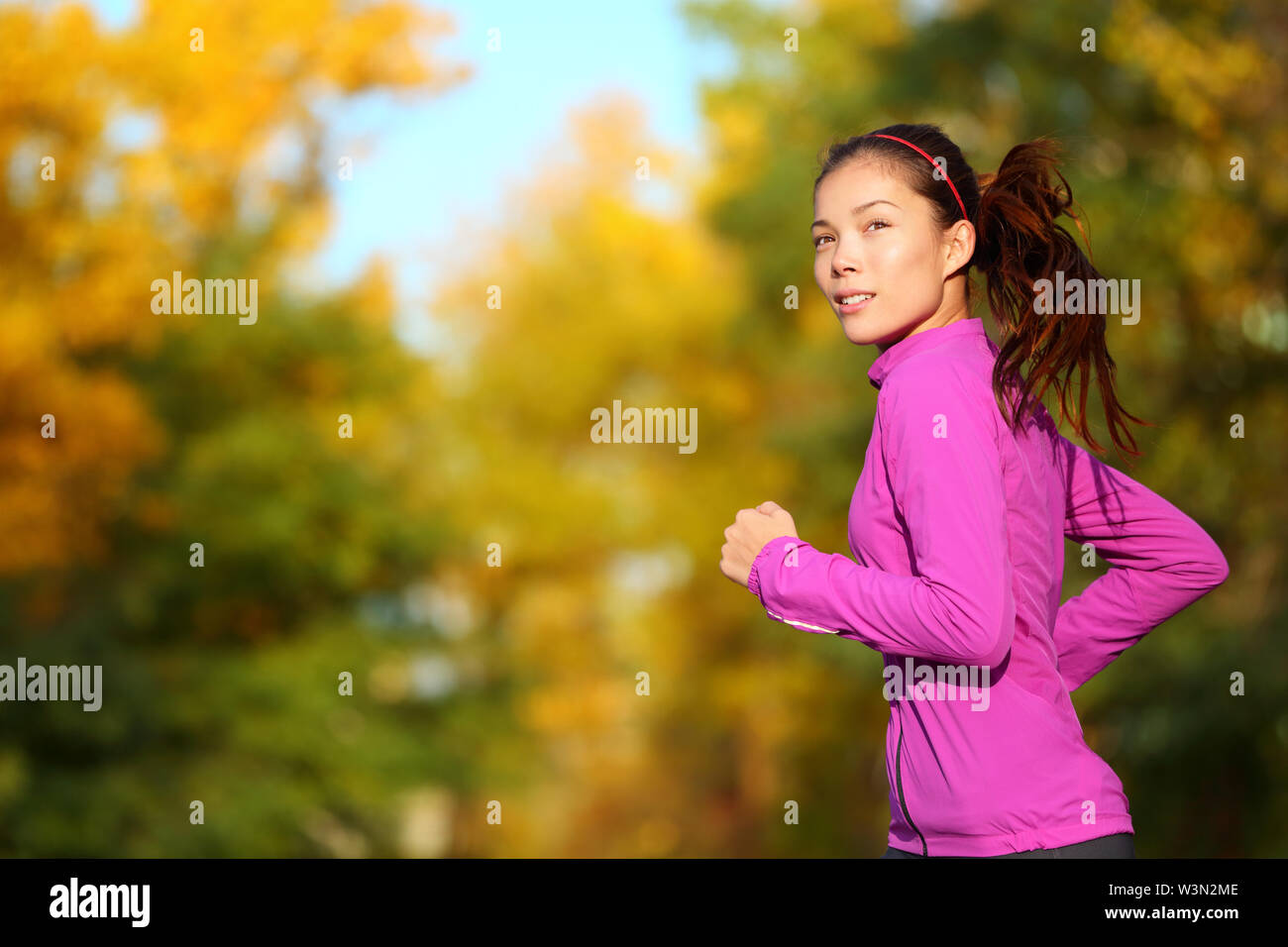 Aspirations - Aspirational woman runner running looking and thinking about future goals. Female athlete jogging in autumn forest in fall color foliage. Beautiful multiracial Asian Caucasian jogger. - Stock Image