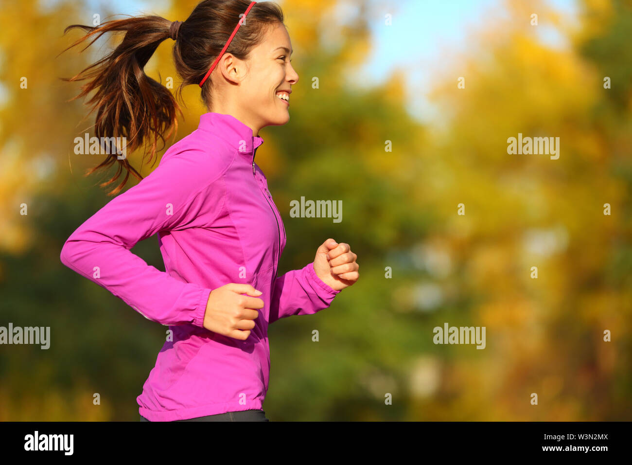 Woman running in autumn fall forest. Female runner training outdoor in profile. Healthy lifestyle image of young Asian woman jogging outside. Fit ethnic Asian Caucasian fitness model. - Stock Image