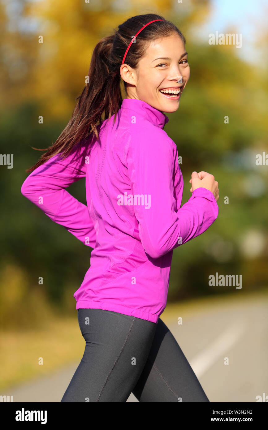 Asian woman running - female runner in autumn forest fall foliage colors. Jogging fit sports fitness girl smiling laughing happy looking at camera. Beautiful energetic mixed race Asian Caucasian model - Stock Image