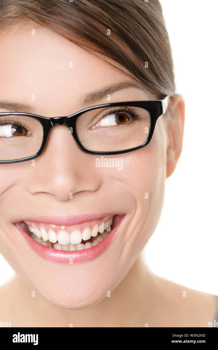 Glasses eyewear spectacles woman looking happy to side with big smile wearing eyeglasses. Close up portrait of female model face isolated on white background. Mixed race Asian Caucasian female model. Stock Photo