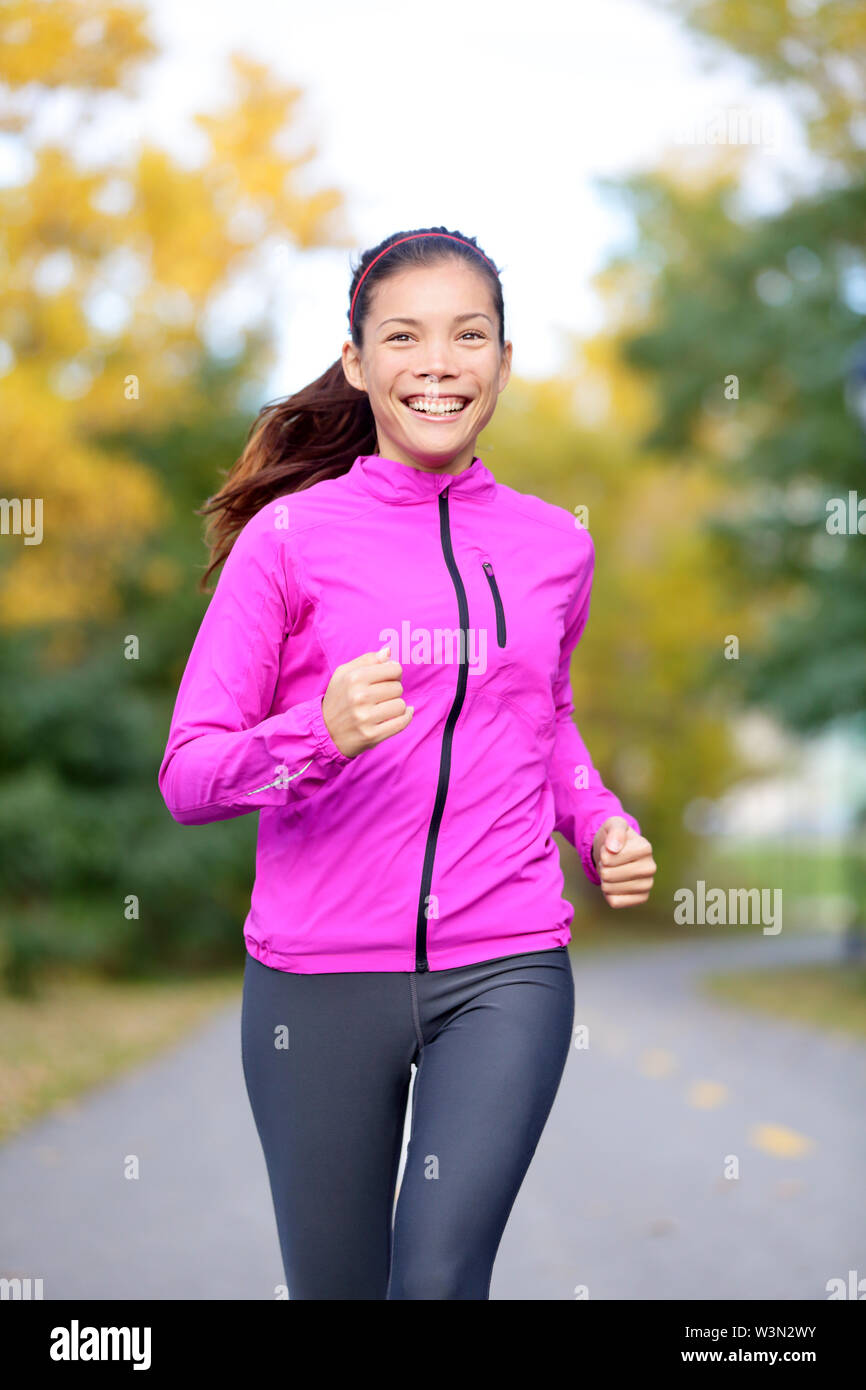 Running sport woman training in fall autumn forest or city park smiling happy. Asian female jogger working out outdoor energetic and fresh. Mixed race Asian Caucasian female fitness model. - Stock Image