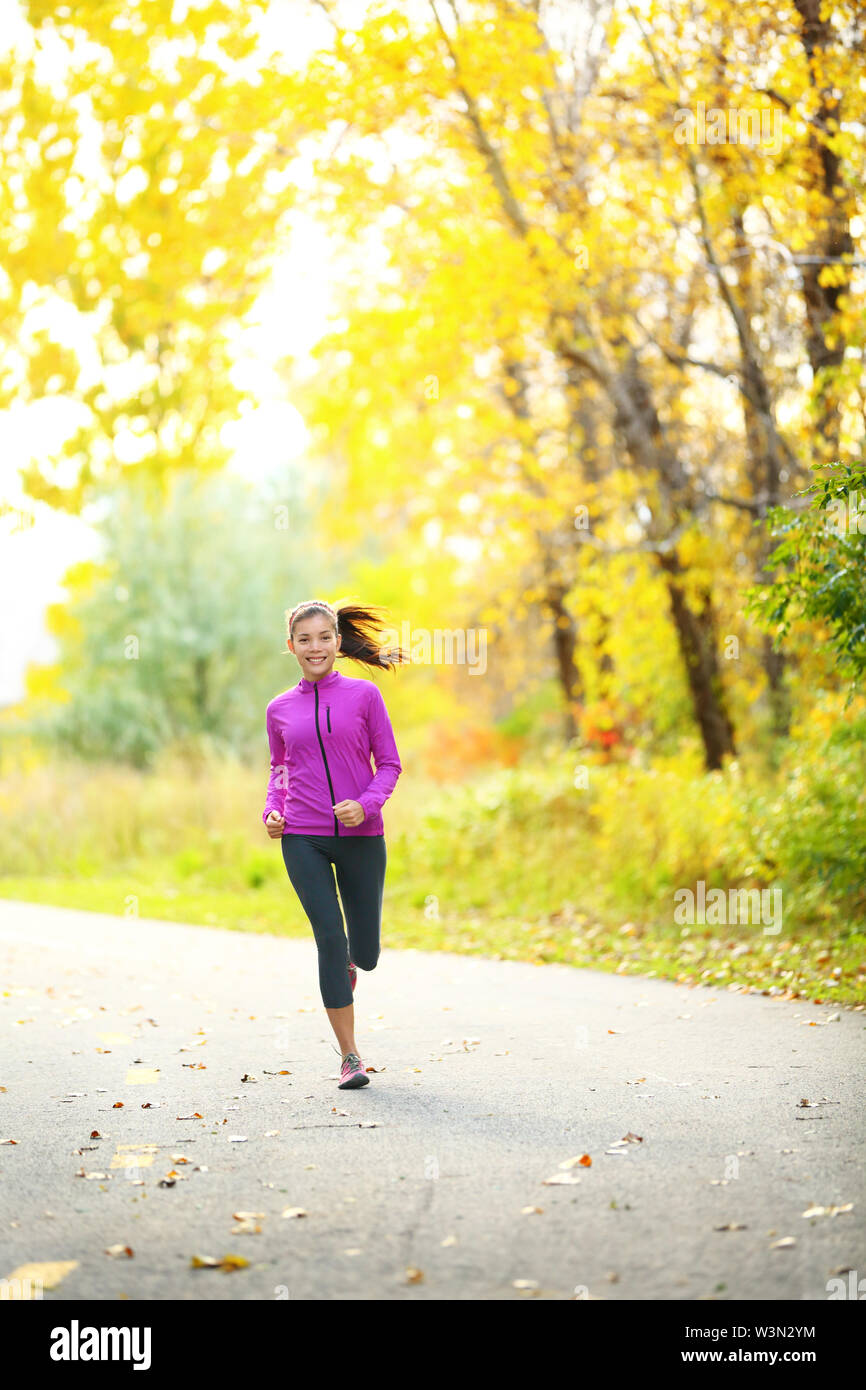 Autumn lifestyle woman running in fall forest with beautiful yellow leaves foliage. Full length portrait of runner jogging outdoor on forest road. Mixed race Asian Caucasian girl in her 20s. - Stock Image