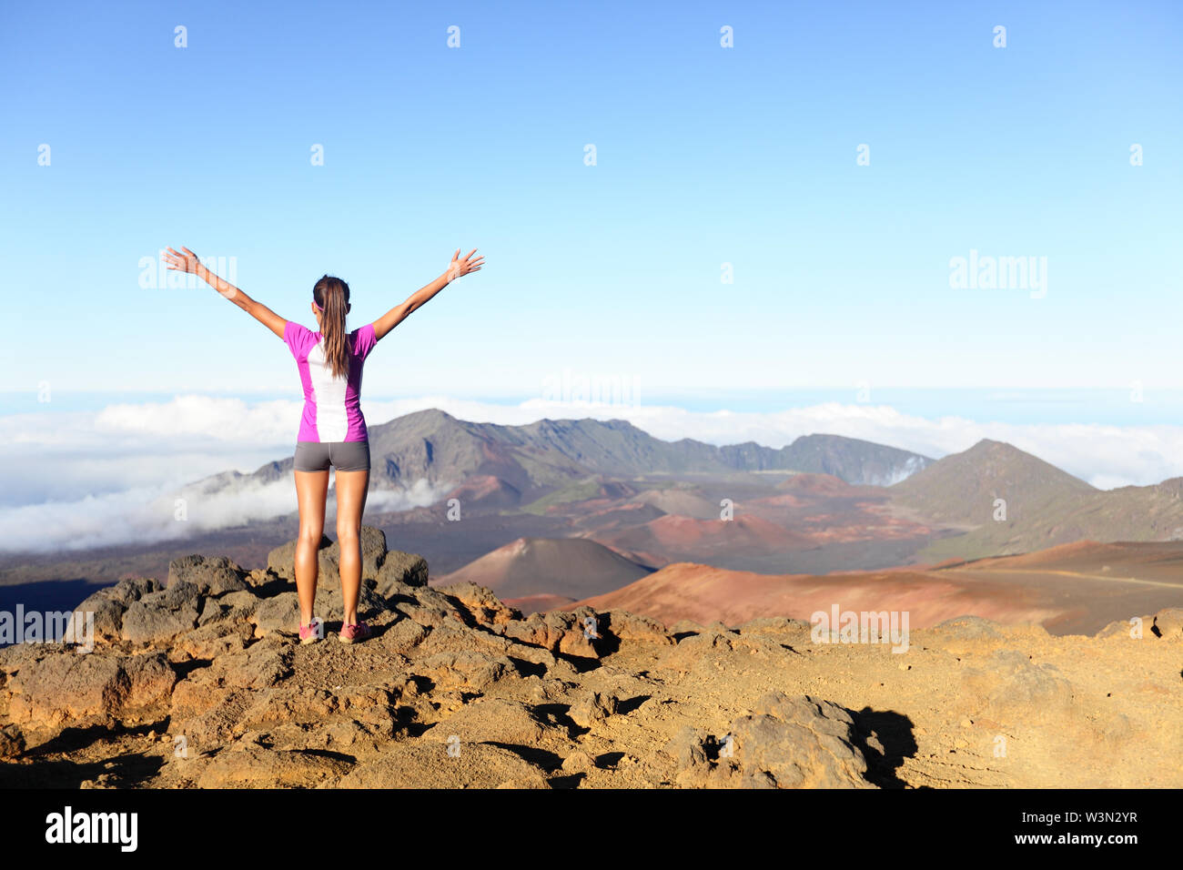 Hiking woman on top happy and celebrating success. Female hiker on top of the world cheering in winning gesture having reached summit of mountain East Maui Volcano Haleakala national park Hawaii. - Stock Image
