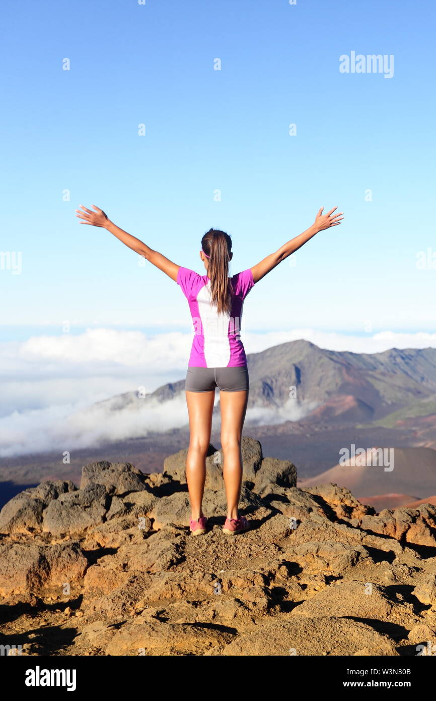 Success and achievement - hiking woman on top of the world. Happy cheering woman in winning gesture excited having reached summit of mountain East Maui Volcano Haleakala national park Hawaii. - Stock Image