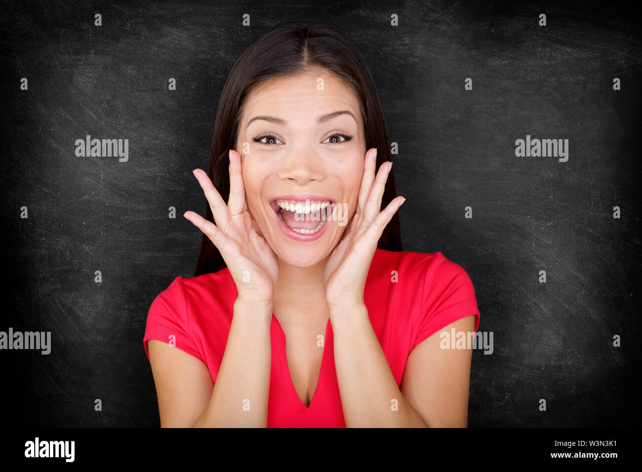 Woman by blackboard / chalkboard excited happy screaming with joy your message with copy space for text. Beautiful young asian multiracial causal female in red on black background. - Stock Image