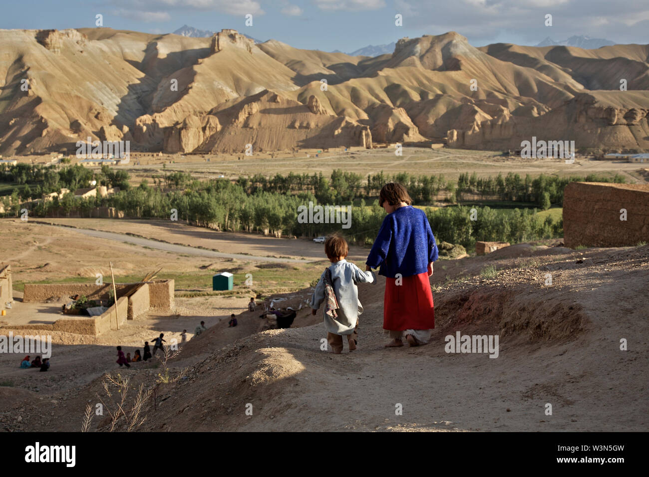 Aqila, 8, leads her 18 month old brother, Abdul Wahid, down the hill, towards other children who are playing in the village of Ragshad, in the central Bamyan Province. Their father works as a daily laborer and the seven children of the family must work up to eight hours a day weaving carpets besides attending school. It takes two months for the family to make a 5 square-meter carpet, worth 800 Afghans, about US $24. The house has no running water or gas, so the older boys walk two hours every day to collect water from a local stream and firewood from the mountains. Ragshad, Bamyan province, Af - Stock Image