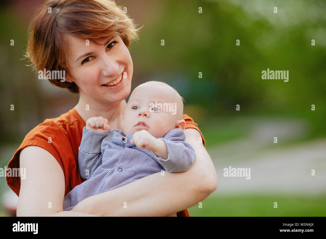 Young cheerful short haired mother in park holding baby in arms looking at camera - Stock Image
