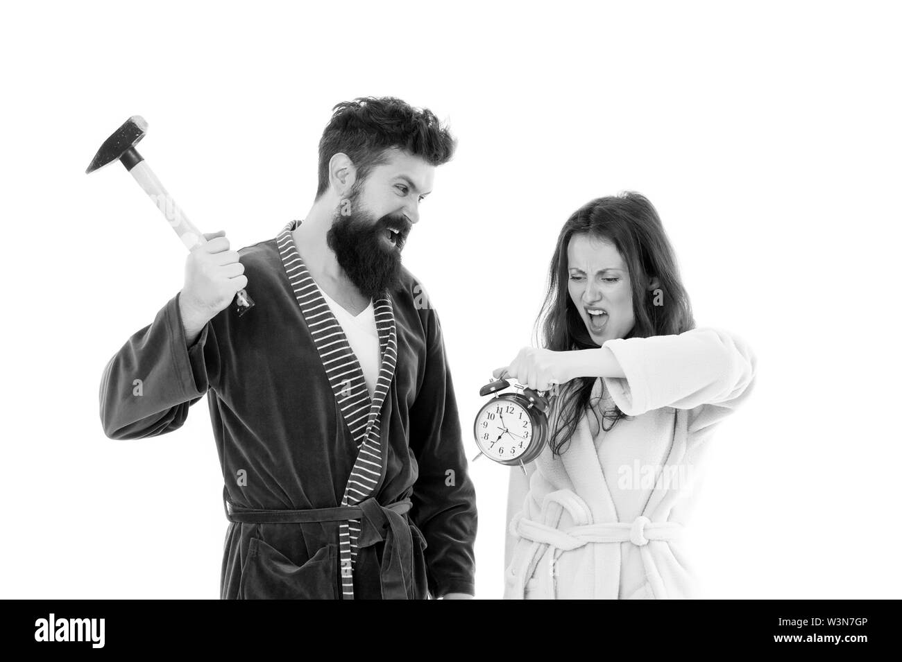 Its early time. Sleepy couple in love in morning time. Angry hipster and woman breaking alarm clock with hammer, lost time. Time will show. - Stock Image