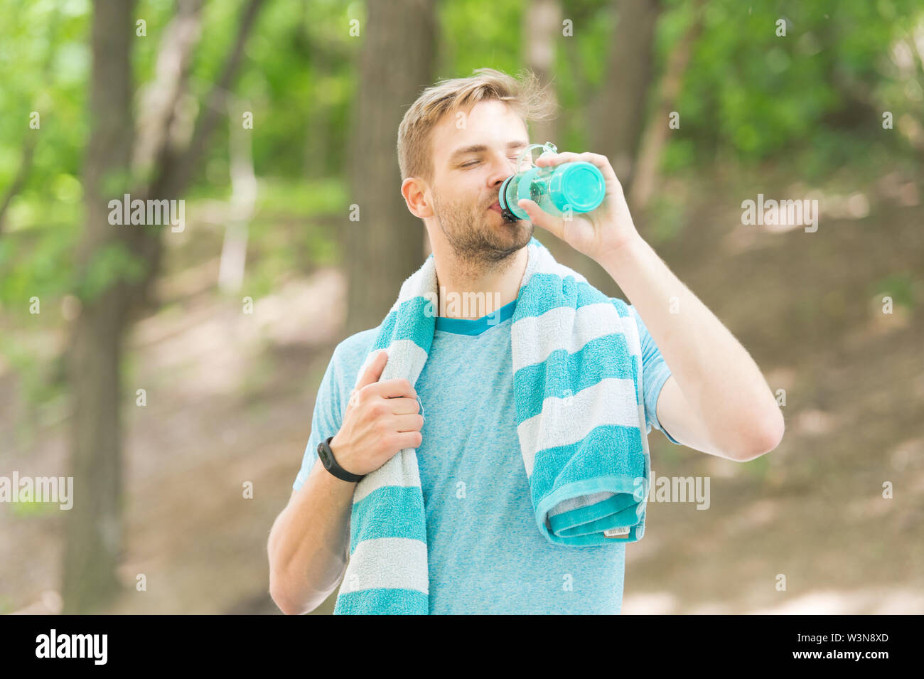 Water is indispensable for human health. Fit athlete having a drink from water bottle during training outdoor. Thirsty sportsman drinking pure water on hot summer day. Keeping body water balance. - Stock Image
