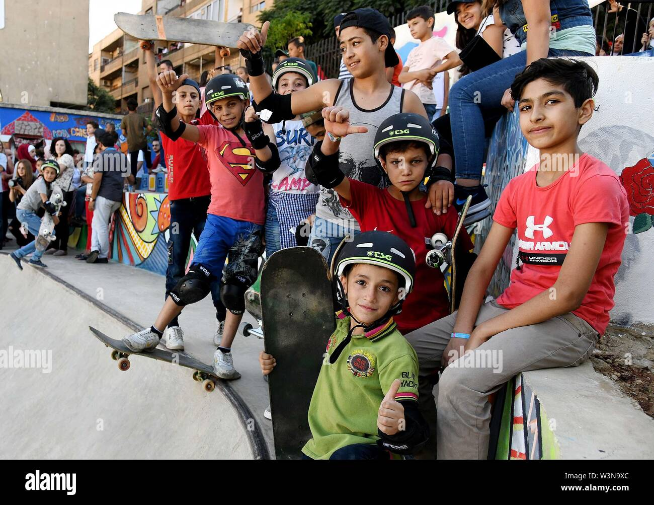 """(190717) -- DAMASCUS, July 17, 2019 (Xinhua) -- Children pose for photos during the opening of the first skatepark in Damascus, Syria, July 15, 2019. The skatepark was co-built by SOS Children's Villages in Syria, the German Skate Aid Foundation and Wonders Around the World, an international and independent non-profit organization. The park, which was officially opened on Monday, was completed in 26 days in an abandoned space close to a residential area that witnessed some acts of rebellion in the early years of the eight-year war in Syria. TO GO WITH """"Feature: First skatepark adds new dimensi Stock Photo"""