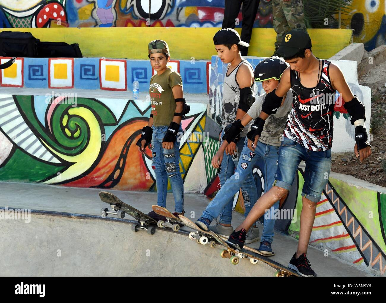 "(190717) -- DAMASCUS, July 17, 2019 (Xinhua) -- Boys skateboard during the opening of the first skatepark in Damascus, Syria, July 15, 2019. The skatepark was co-built by SOS Children's Villages in Syria, the German Skate Aid Foundation and Wonders Around the World, an international and independent non-profit organization. The park, which was officially opened on Monday, was completed in 26 days in an abandoned space close to a residential area that witnessed some acts of rebellion in the early years of the eight-year war in Syria. TO GO WITH ""Feature: First skatepark adds new dimension to Syr Stock Photo"