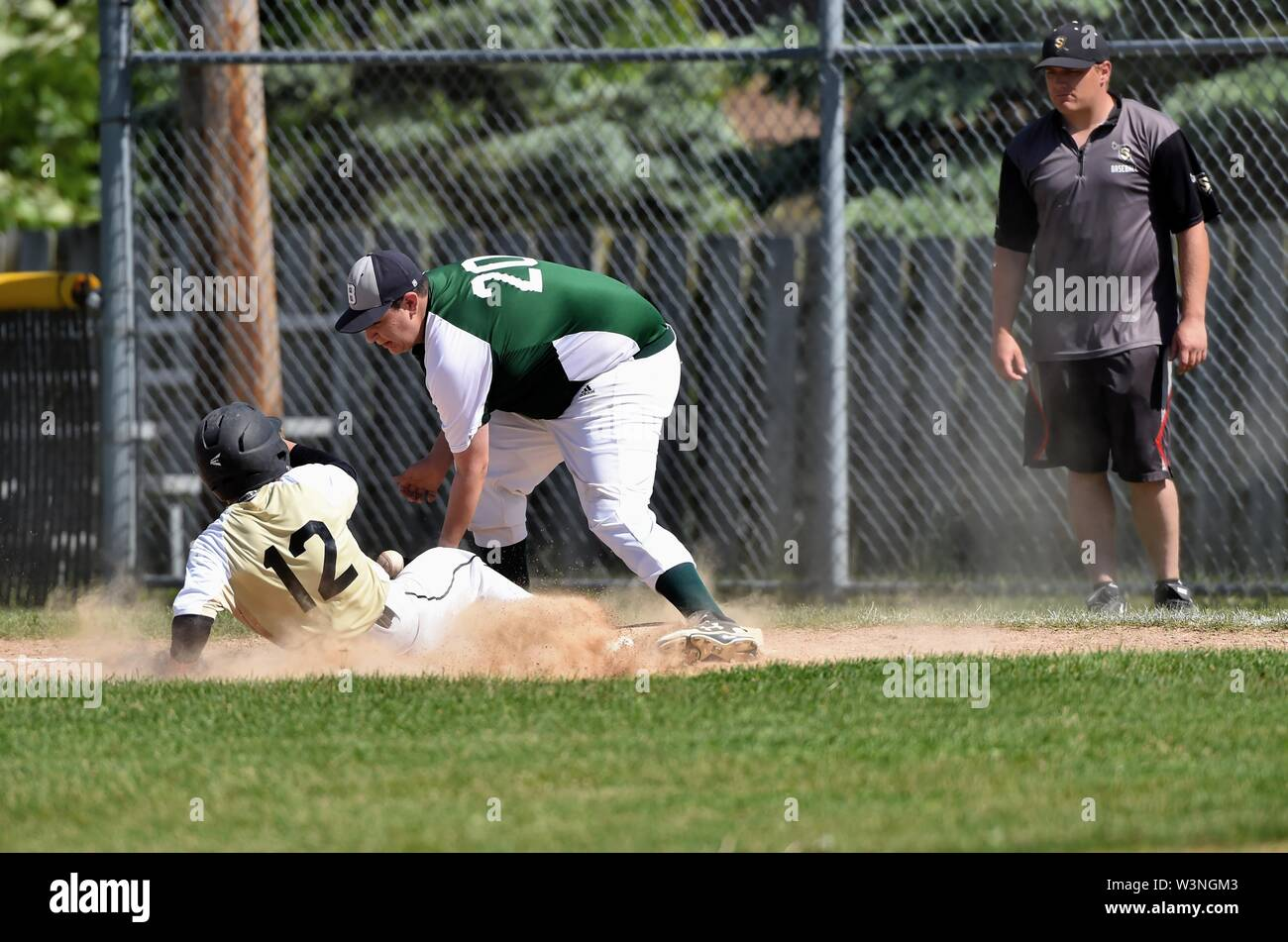 The Sabres' Colim Blanchard sliding safely back into first base to avoid a double play man nas the Hawks; first baseman Denny Garza was unable to secu - Stock Image