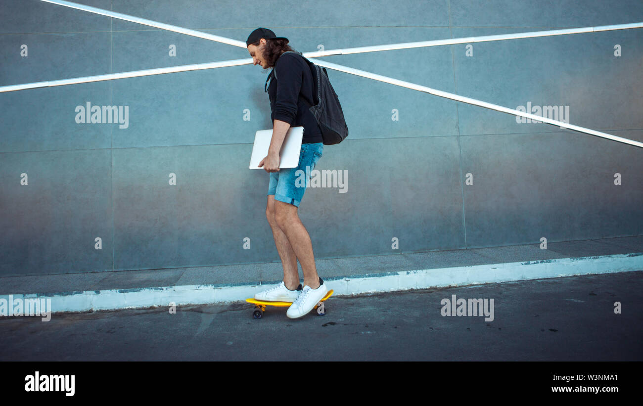 A young man in a baseball cap, with a backpack, and in denim shorts with a laptop under his arm, drives past a gray granite wall with white stripes. C - Stock Image