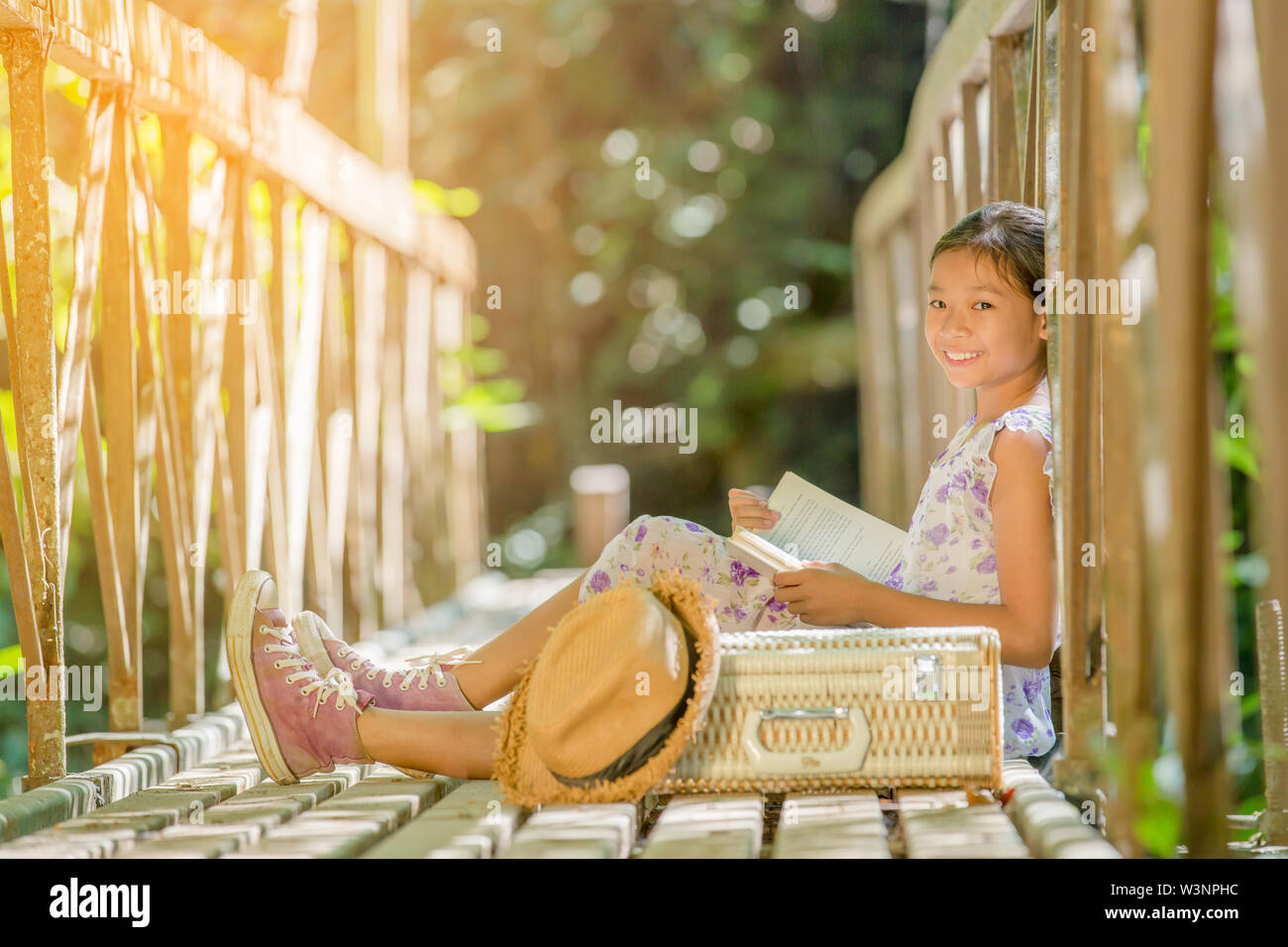 asian girl reading book on the old bridge in the forest - Stock Image