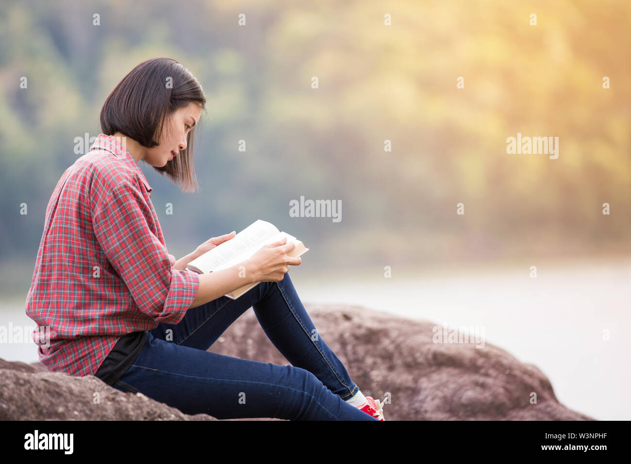 beautiful woman reading a book in the nature - Stock Image