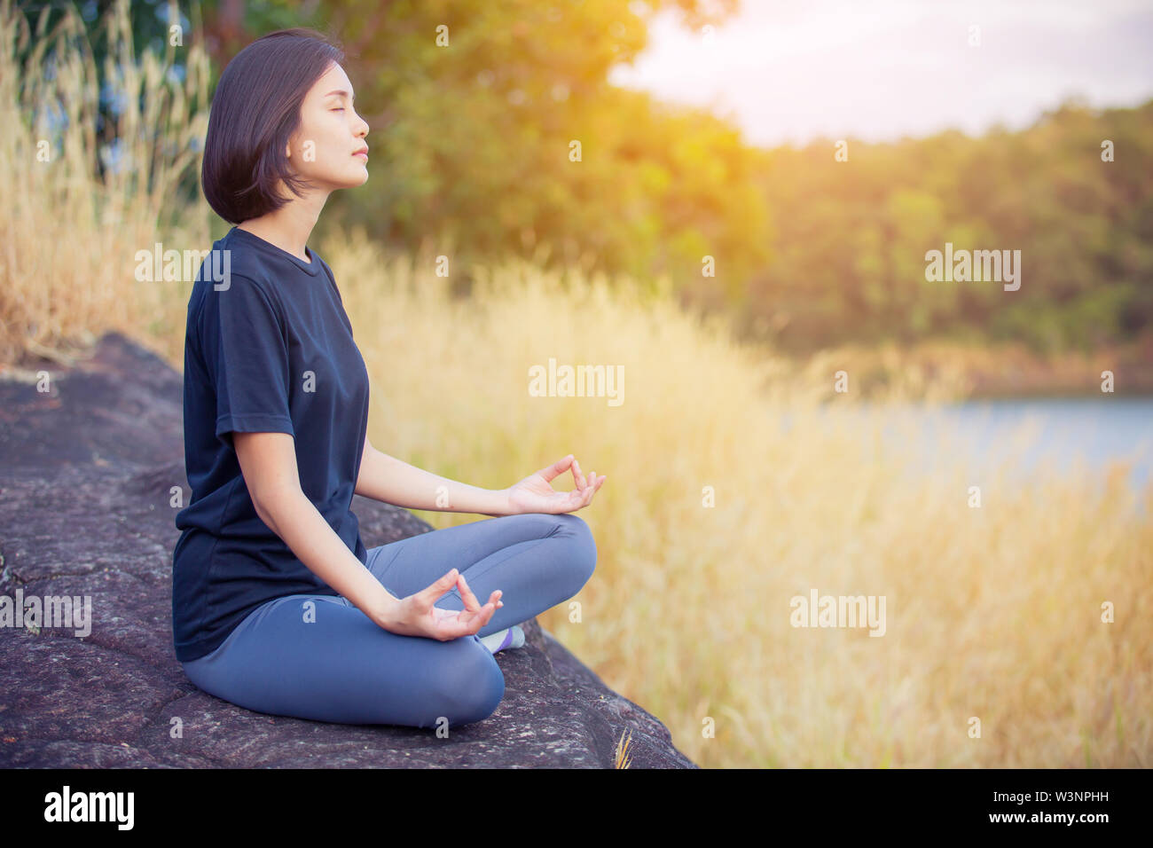 asian woman Yoga relax in nature to relax outdoor - Stock Image