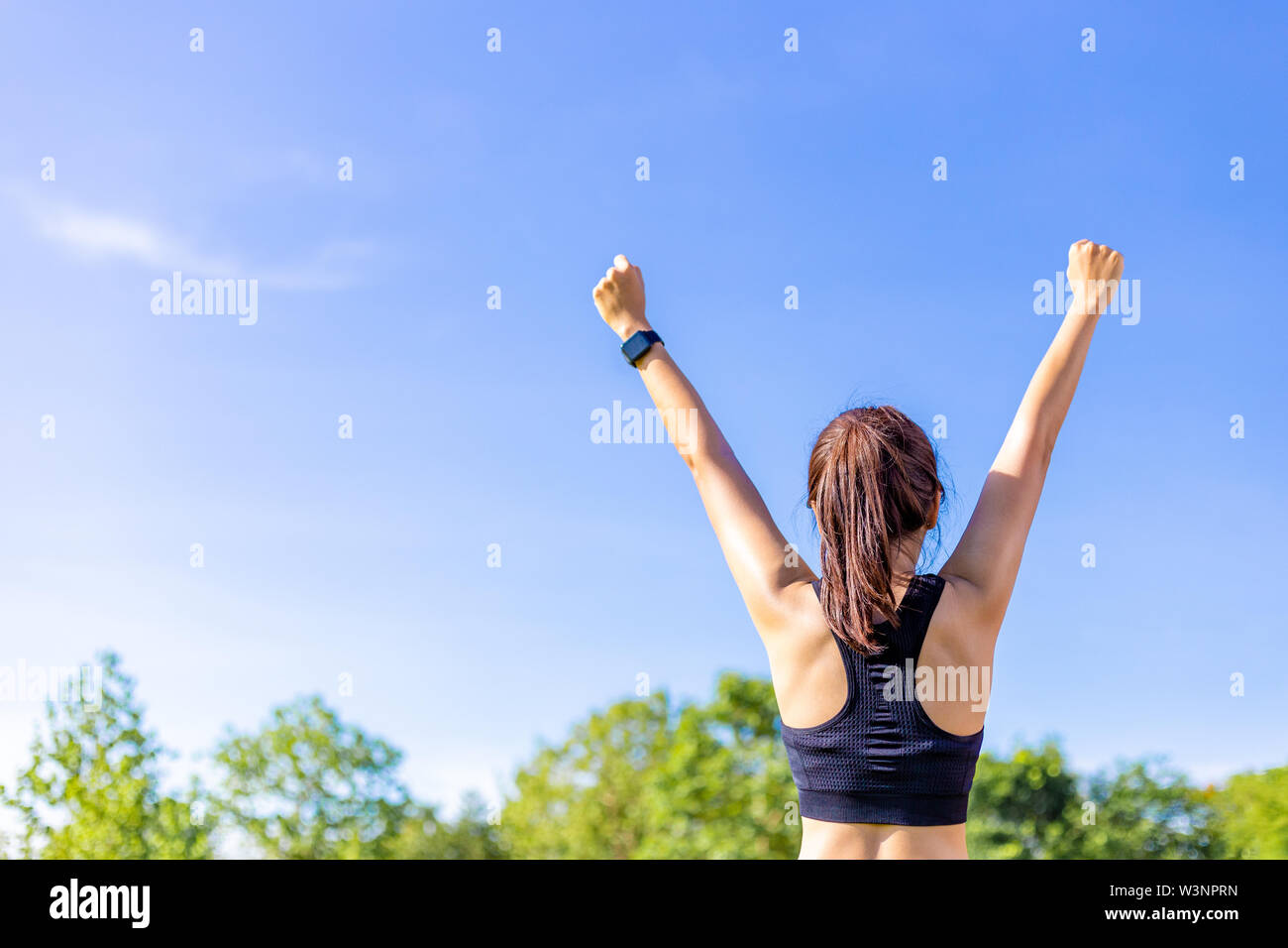 Back view of a woman in stretching up her arms and fists happily at an outdoor field with blurred trees and clear blue sky background on a bright sunn - Stock Image