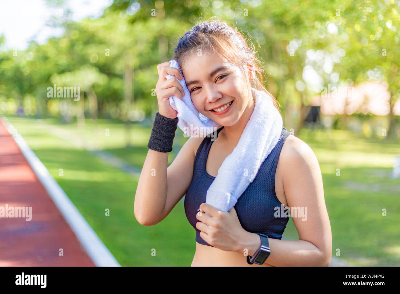 Beautiful young happy healthy Asian woman using her white towel to wipe of her sweat after her running exercise in the morning at a running track, blu - Stock Image