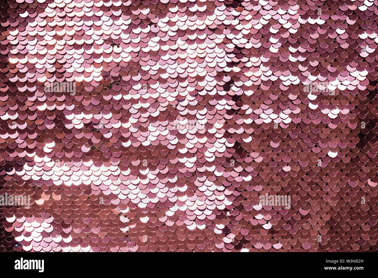 Luxury abstract background with coral iridescent sequins on fabric. - Stock Image