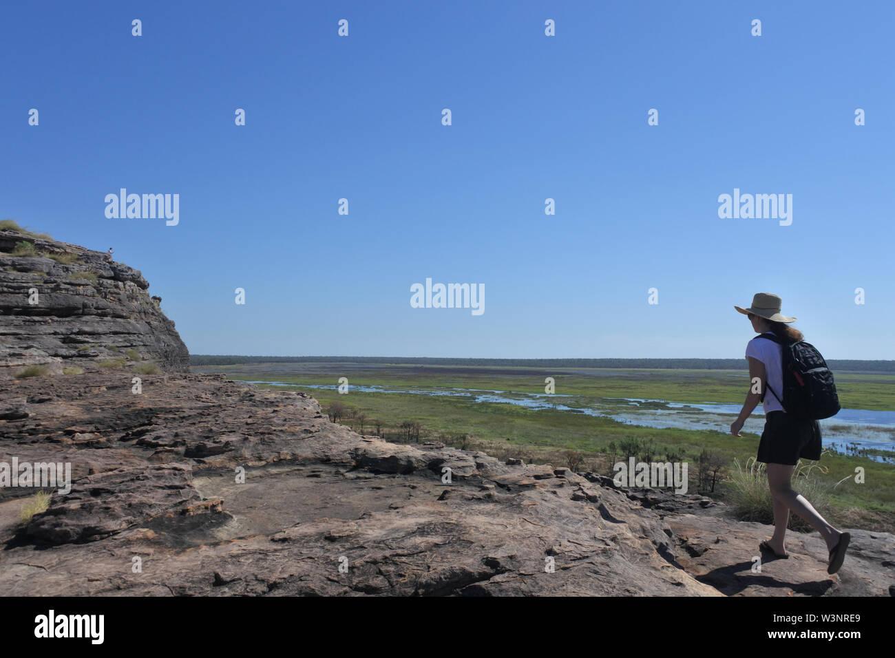 Australian adult woman tourist hiking at Ubirr rock art site in Kakadu National Park Northern Territory of Australia. - Stock Image