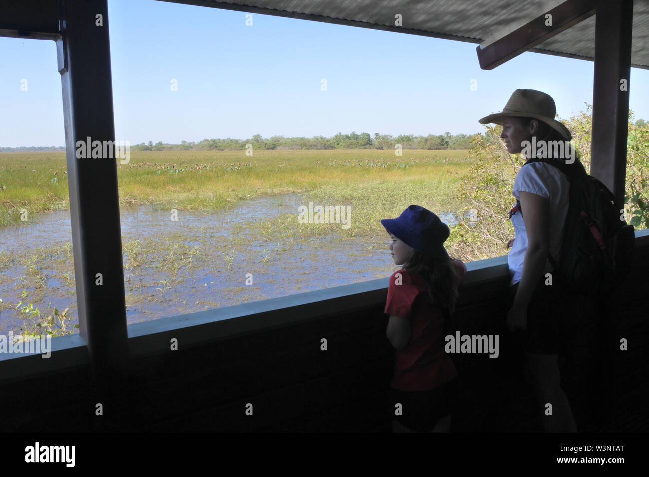Australian mother and daughter looking a the landscape view of wetland swamp in Kakadu National Park Northern Territory Australia - Stock Image