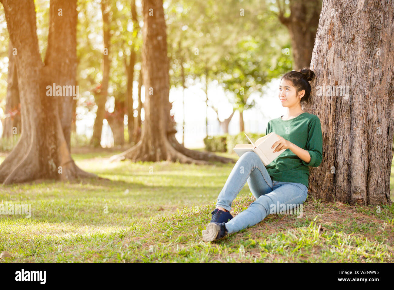 Beautiful young asian woman sitting and reading book in a park - Stock Image