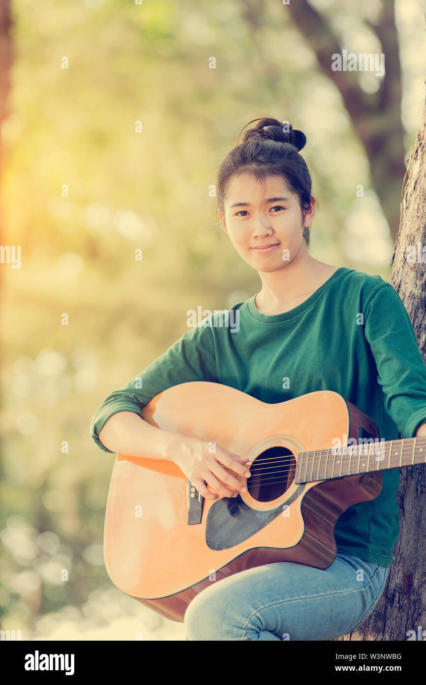 Young asian girl in forest with guitar, selective focus - Stock Image