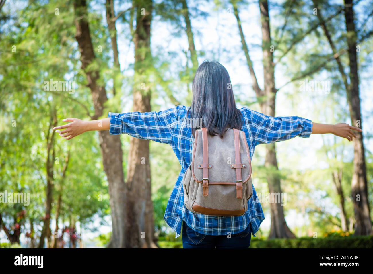 Young woman arms raised enjoying the fresh air in green forest. - Stock Image
