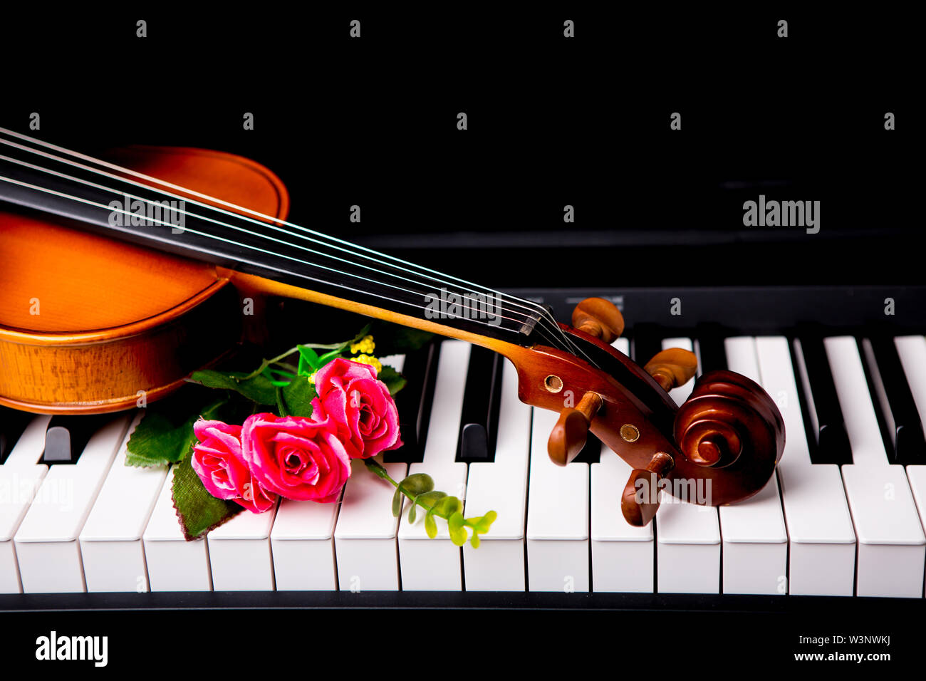 Violin on the piano on a black background - Stock Image