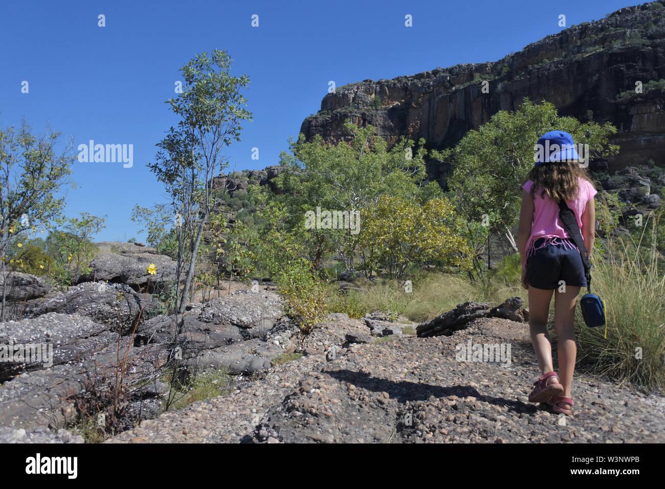 Young Australian girl (age 8-9) hiking at Burrungkuy Nourlangie rock art site in Kakadu National Park Northern Territory of Australia - Stock Image