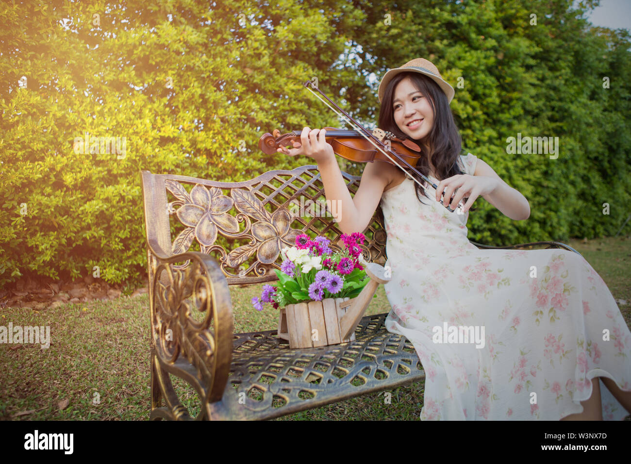 asia woman playing violin in garden - Stock Image