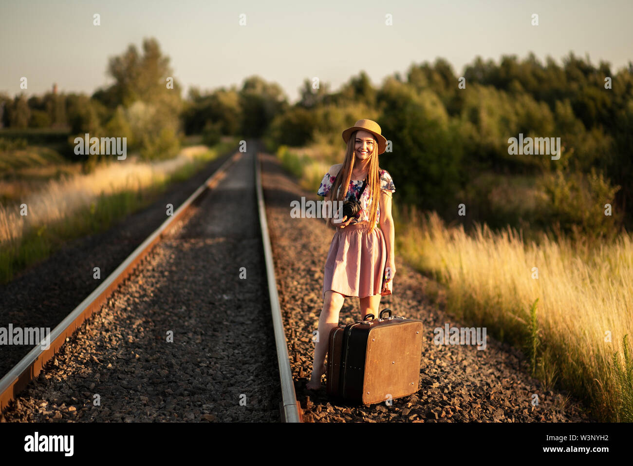 slim girl in a straw hat standing with suitcases on the railroad tracks, with a camera, smiling and dreaming. The concept of travel, happiness, freedo - Stock Image