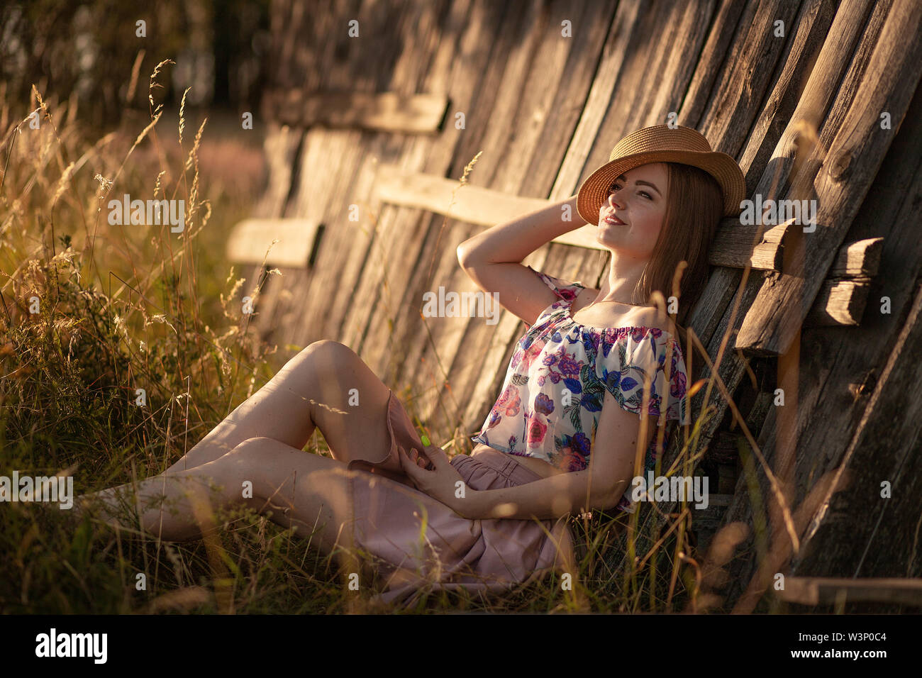 beautiful slender girl with long hair in a straw hat sitting near a wooden fence and dreaming. Summer evening at sunset. Love concept happiness, youth - Stock Image