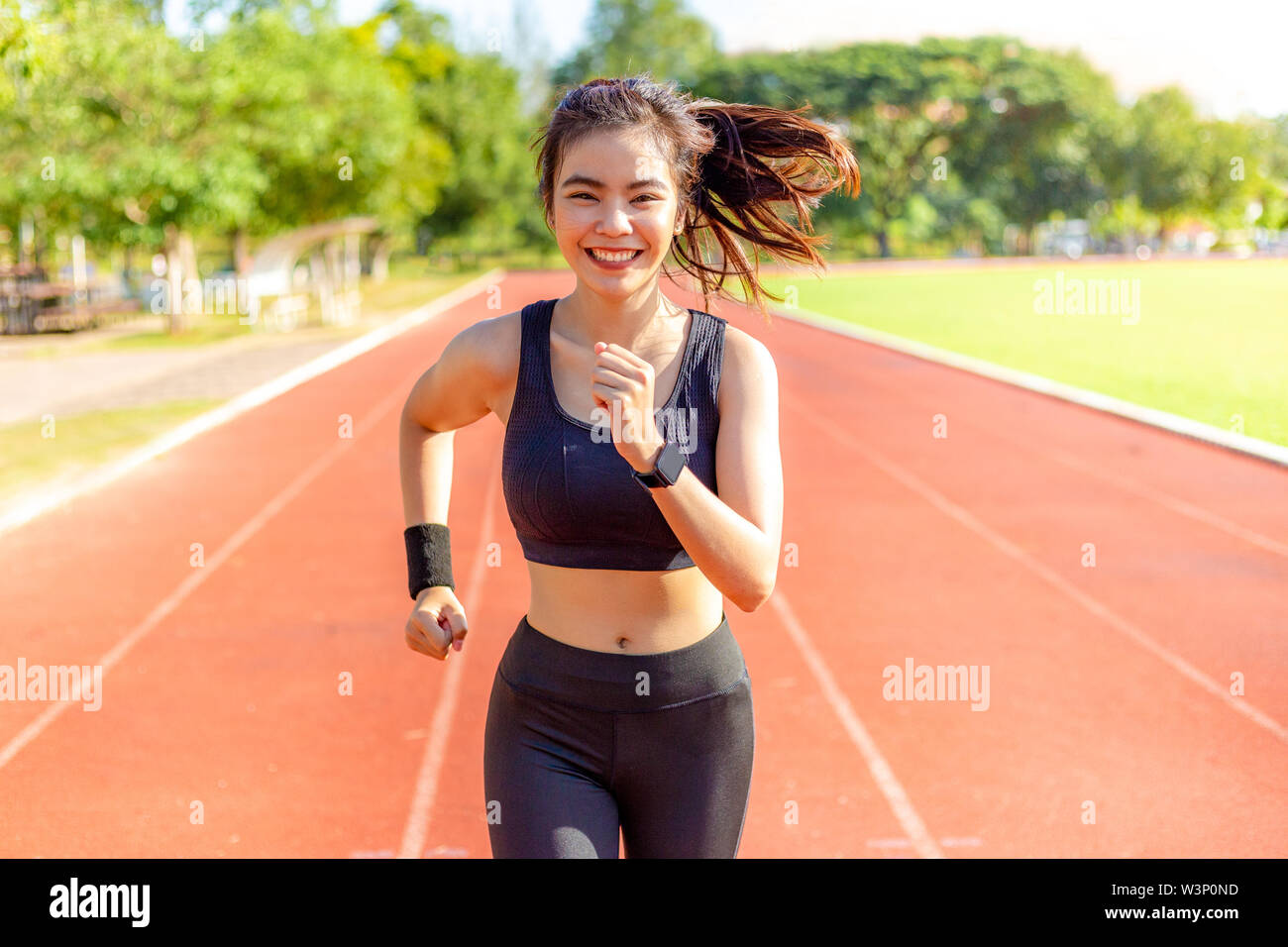 Beautiful happy young Asian woman running for her morning exercise at a running track with blurred track and trees in background, healthy lifestyle - Stock Image