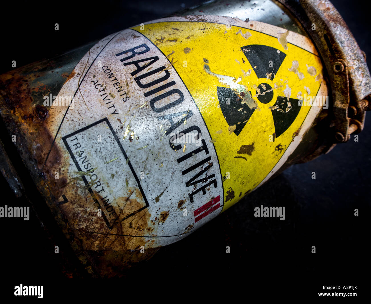 Radiation warning sign on transport index label stick on the rust and decay radioactive material container - Stock Image