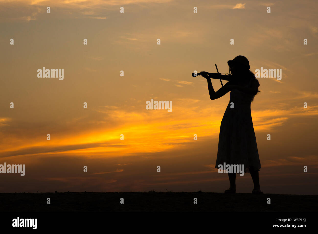 silhouette of asian woman play violin on sunset - Stock Image