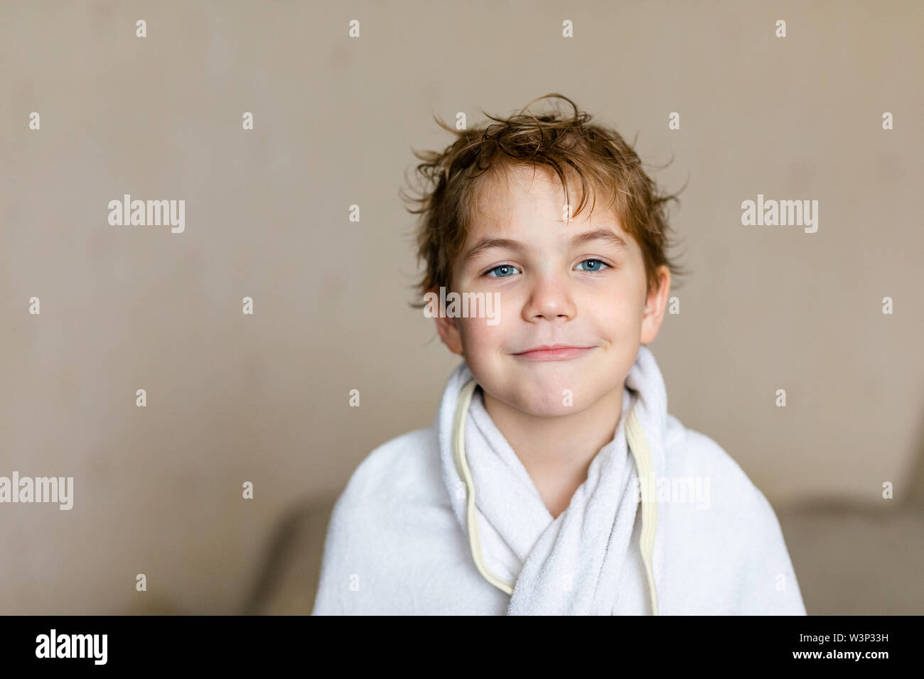 Blode caucasian boy after bath with wet hair and white towel on the head. Funny face, great smile, positive mood. - Stock Image