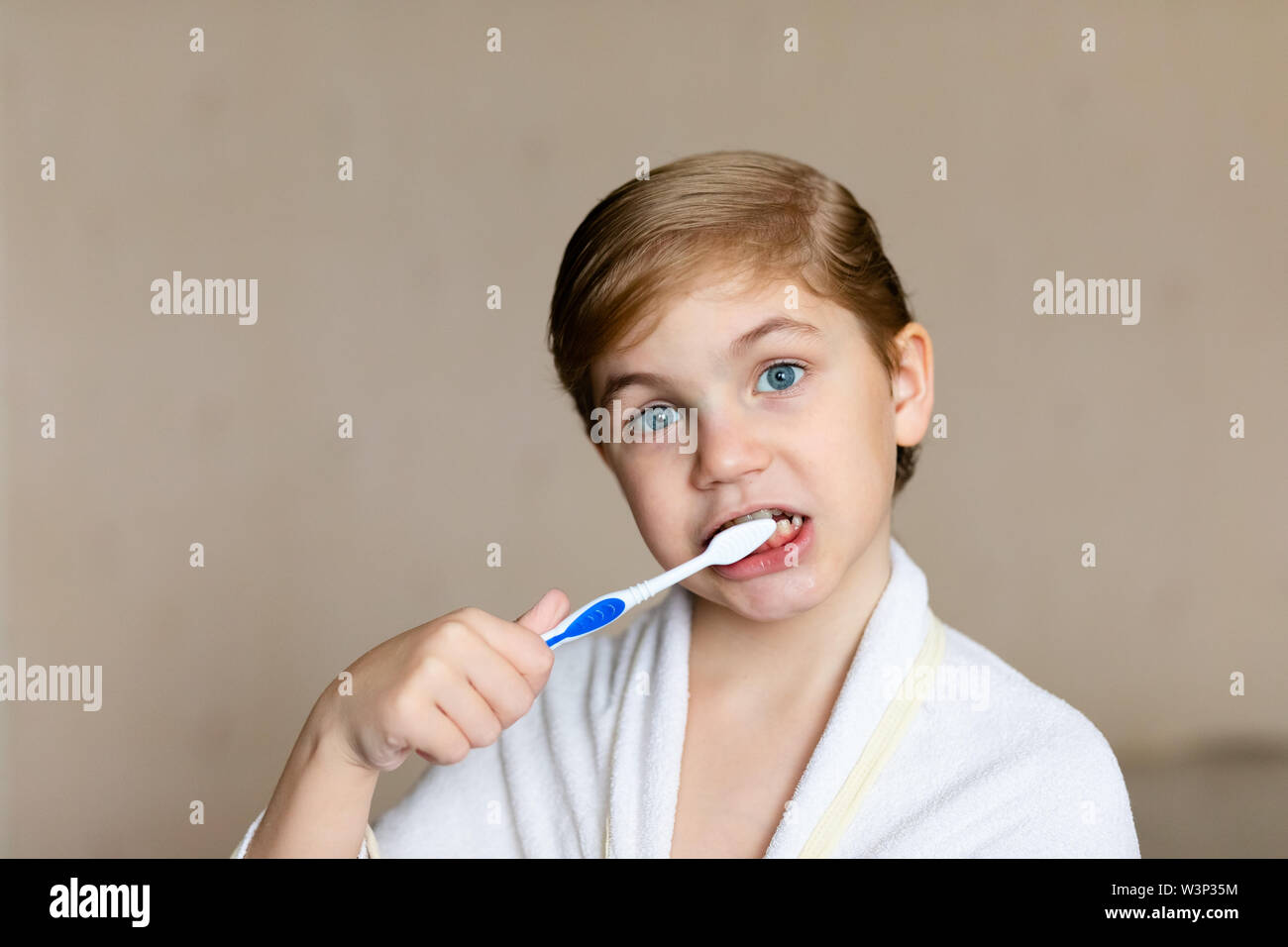 A cute little blonde boy with blue eyes brushing his teeth with a toothbrush. The concept of children's health, medicine. - Stock Image