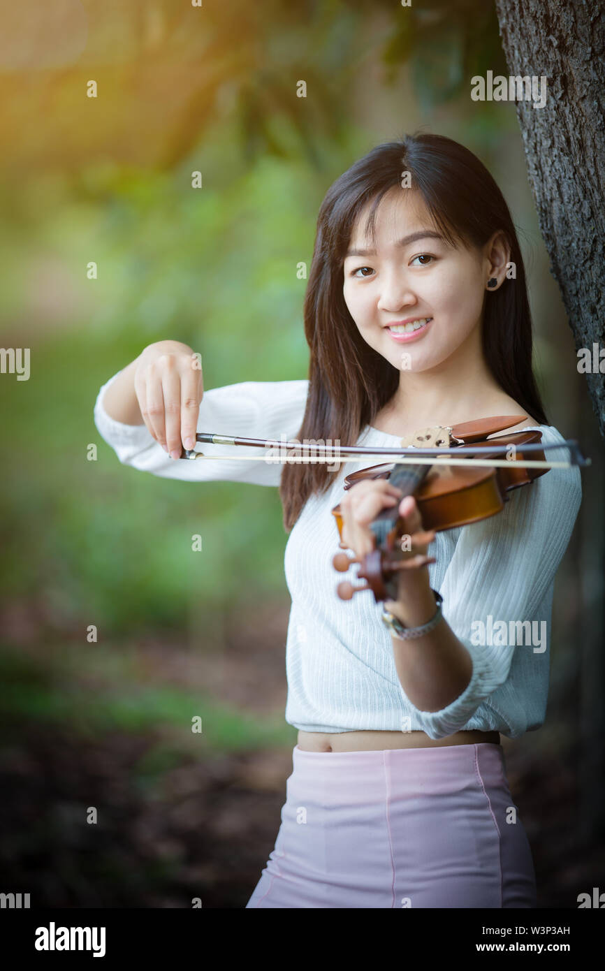 asia woman playing violin in garden with sunshine - Stock Image