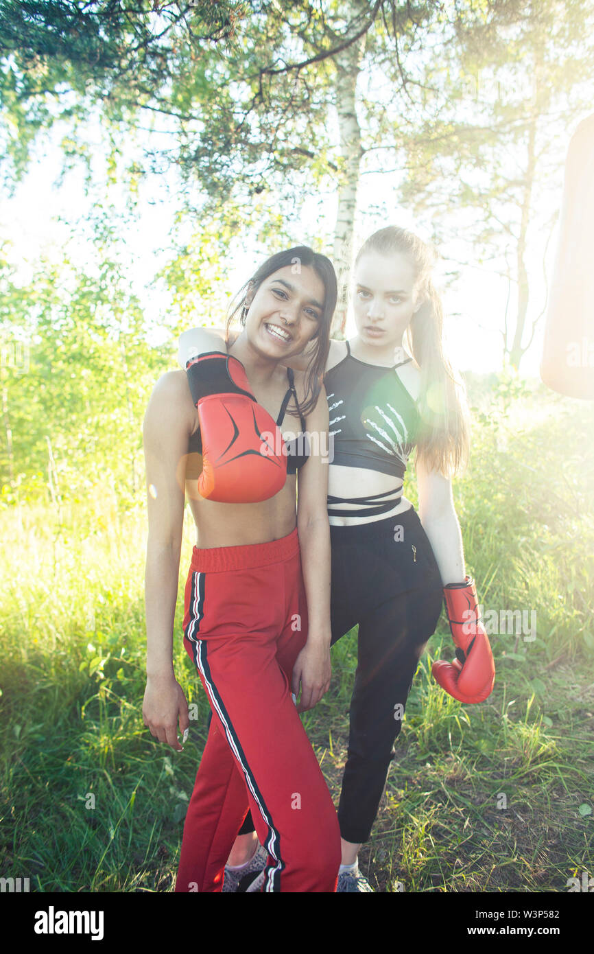 two diverse nations girls fighting boxing outside in green park, sport summer people concept - Stock Image