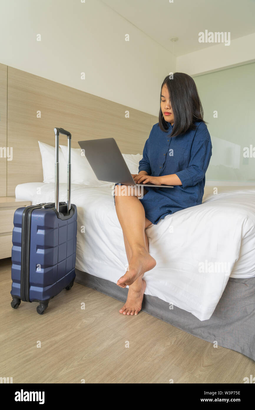 Freelancer woman using laptop on bed in business trip  Stock Photo