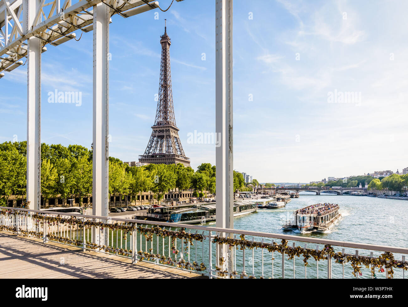 The Eiffel tower in Paris, France, seen from the Debilly footbridge on a sunny summer afternoon with a tourist river boat cruising on the river Seine - Stock Image