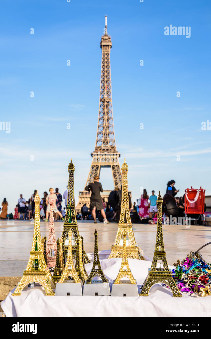 The Eiffel tower in Paris, France, pictured with miniature Eiffel towers in the foreground, sold on the Trocadero esplanade by street vendors. - Stock Image