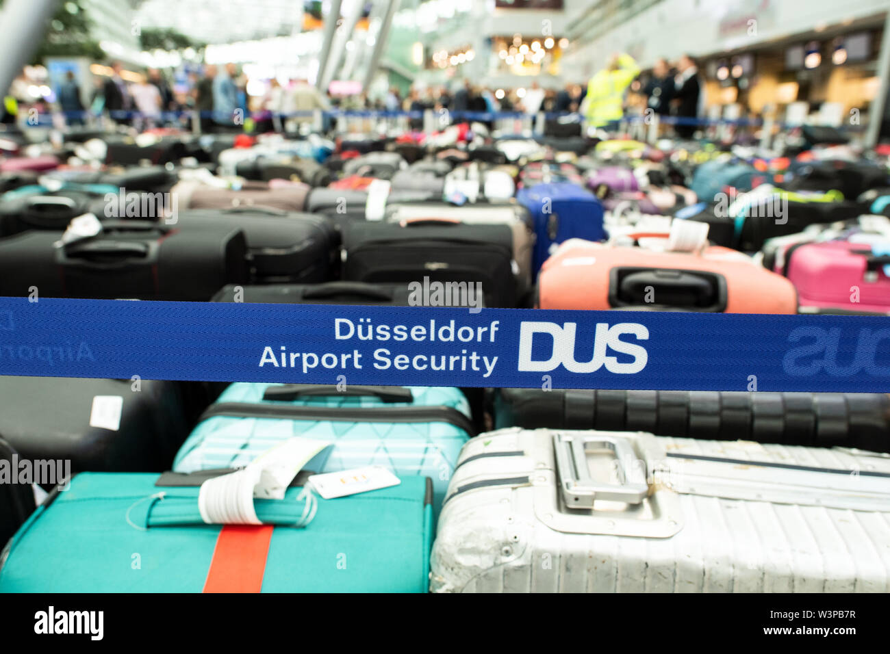 Duesseldorf, Germany. 17th July, 2019. Several hundred pieces of baggage are standing in the departure hall of Düsseldorf Airport, blue ribbons with the inscription Düsseldorf Airport DUS close off the area. Due to a technical malfunction, passengers at Düsseldorf Airport have to be prepared for problems with baggage handling. Credit: Federico Gambarini/dpa/Alamy Live News - Stock Image
