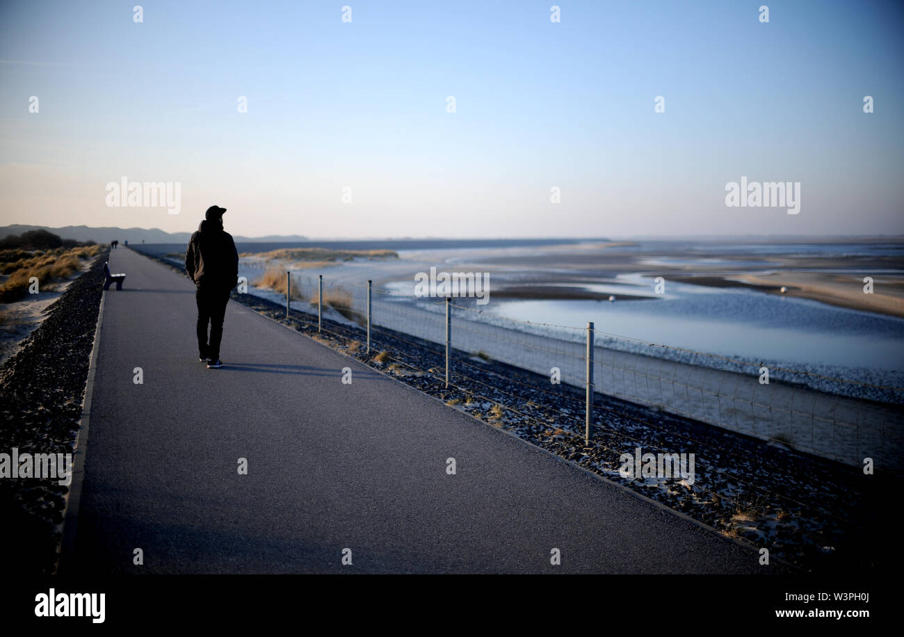 Sylt, Germany. 17th Feb, 2019. A young man goes for a walk on the dam on the island of Sylt. Sylt is the largest North Frisian island in Germany. Credit: Britta Pedersen/dpa-Zentralbild/ZB/dpa/Alamy Live News - Stock Image