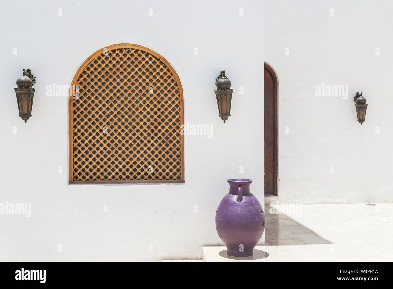 Arabian white building with wooden lamps and jug. - Stock Image