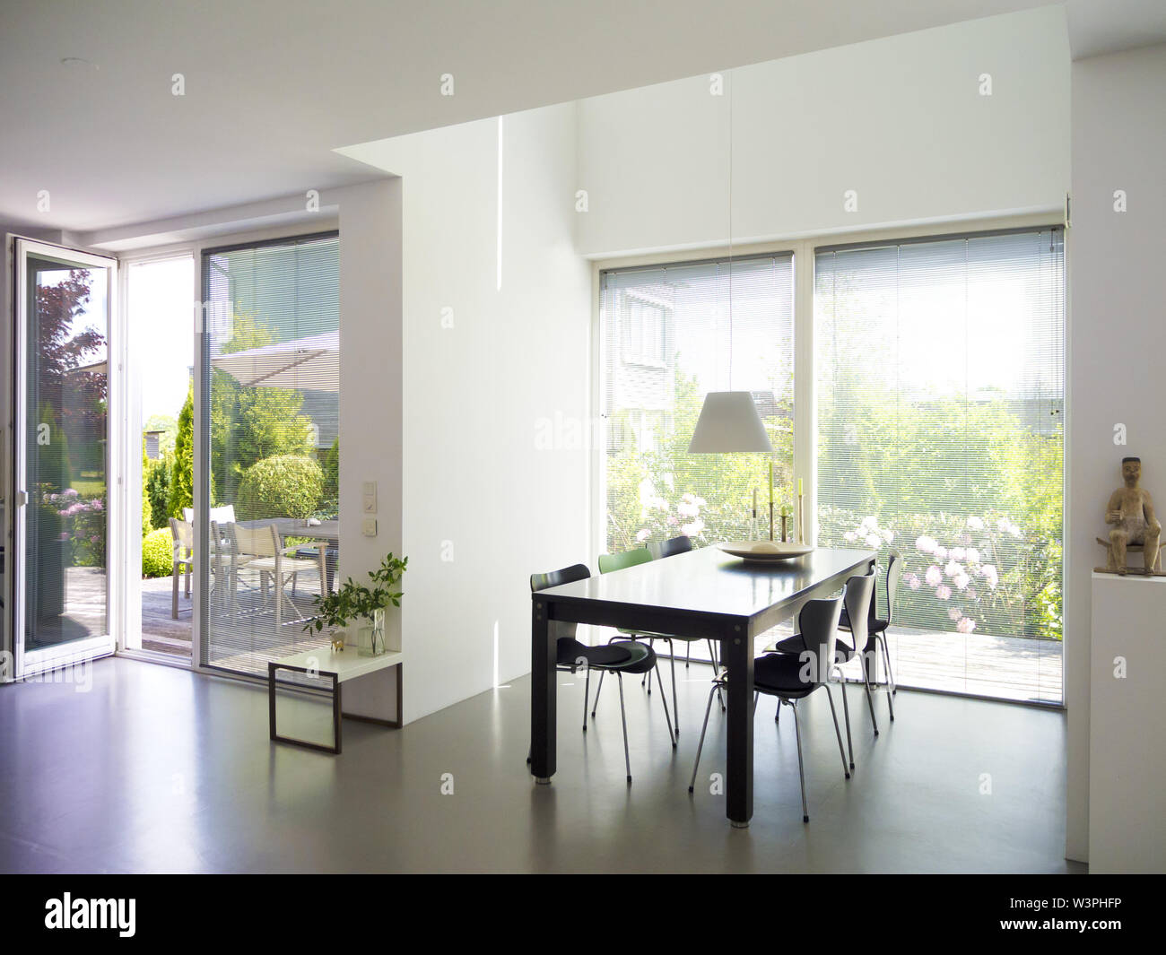 Modern Contemporary Dining Room Interior With Concrete Floor French Doors And Windows And A View To The Terrace And The Garden Stock Photo Alamy