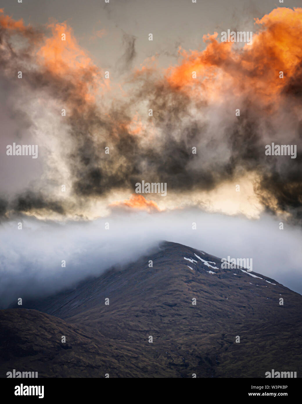Setting sun light up the clouds over mountain peak in Scottish Highlands.Beautiful sunset scene with colourful and dramatic sky. - Stock Image